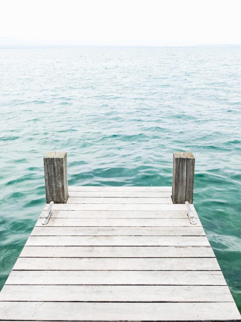 End of dock overlooking ocean or lake water