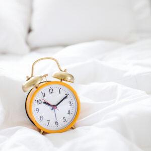 yellow alarm clock on bed