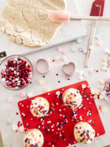 baking scene with cupcakes, sprinkles, and a bowl of candy