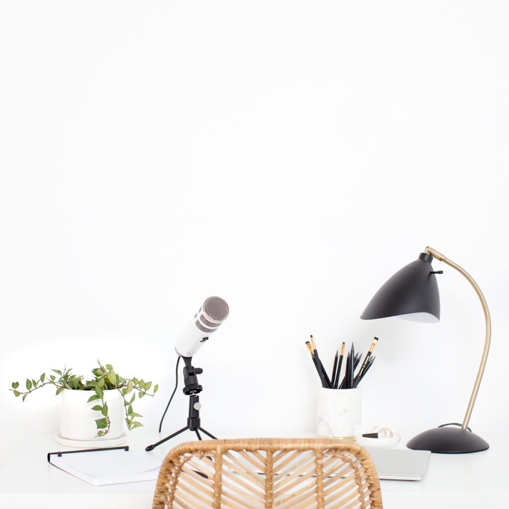 Desk with podcast microphone, plant, and lamp